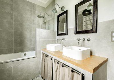 Vue sur l'espace de douche et les deux petites vasques
